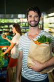 Portrait of smiling man holding a grocery bag in organic section Stock Image