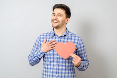Portrait of smiling man holding red paper heart Royalty Free Stock Photos