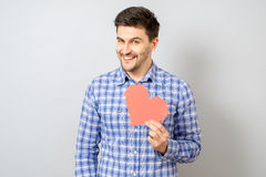 Portrait of smiling man holding red paper pixel heart. On gray background stock photo