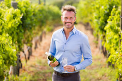 Portrait of smiling man holding wine bottle and glass. At vineyard on sunny day stock photo