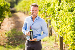 Portrait of smiling man holding wine bottle Stock Images