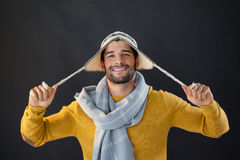 Portrait of smiling man holding wooly hat. Against black background Royalty Free Stock Images