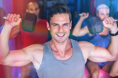 Portrait of smiling man lifting dumbbell in gym Royalty Free Stock Photos