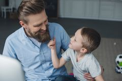 Portrait of smiling man and little son looking at each other. At home stock photo