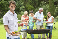 Portrait of smiling man with plate of barbecue and wine glass with family in background. Portrait of smiling men with plate of barbecue and wine glass with Royalty Free Stock Photos