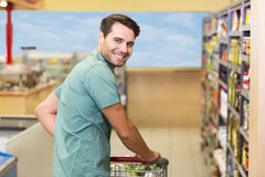 Portrait of smiling man pushing his trolley in aisle Stock Image