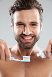 Portrait of a smiling man putting toothpaste on a toothbrush. Close up ortrait of a smiling handsome man putting toothpaste on a toothbrush isolated over white Stock Images