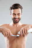 Portrait of a smiling man putting toothpaste on a toothbrush. Portrait of a smiling shirtless man putting toothpaste on a toothbrush isolated over white Stock Image