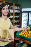 Portrait of smiling man selecting oranges in organic section Stock Photo