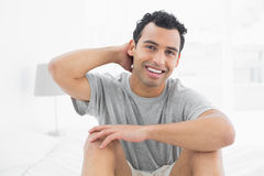 Portrait of a smiling man sitting on bed Royalty Free Stock Images