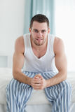 Portrait of a smiling man sitting on his bed Stock Photography