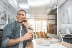 Cheerful male talking by phone. Portrait of smiling man speaking by mobile while drinking cup of coffee in office. Employer working with appliance concept Royalty Free Stock Image