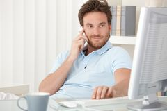 Portrait of smiling man speaking on phone. Portrait of smiling man speaking on mobile phone, sitting at desk, looking at computer screen Royalty Free Stock Photography