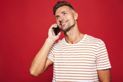 Portrait of a smiling man standing over red background stock photo