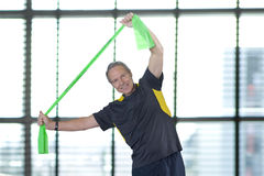 Portrait of smiling man stretching with resistance band overhead Stock Photo