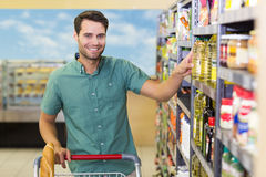 Portrait of smiling man taking oil in the shelf of aisle Royalty Free Stock Photos