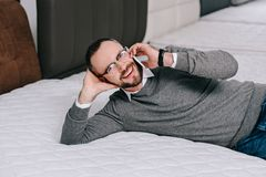 Portrait of smiling man talking on smartphone while lying on mattress. In furniture store stock photography