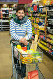 Portrait of smiling man with trolley in grocery section. At supermarket Royalty Free Stock Photo