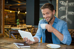 Portrait of smiling man using digital tablet while drinking coffee Stock Photos