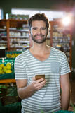 Portrait of smiling man using his phone in the organic section Stock Photography