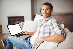 Portrait of smiling man using laptop at home Stock Photo