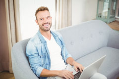 Portrait of smiling man using laptop at home Royalty Free Stock Photography