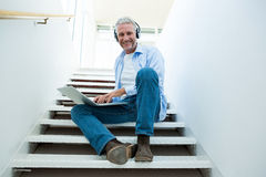 Portrait of smiling man using laptop on steps Royalty Free Stock Image