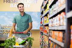 Portrait of smiling man walking in aisle with his trollet Royalty Free Stock Images