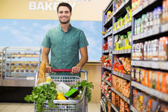 Portrait of smiling man walking with his trolley on aisle. At supermarket Stock Photo