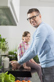Portrait of smiling man washing hands with daughter sitting on counter in kitchen Stock Photography