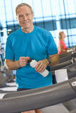 Portrait of smiling man with water bottle leaning on treadmill in health club Royalty Free Stock Images