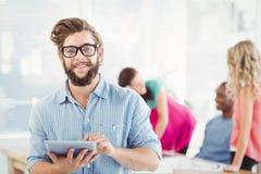 Portrait of smiling man wearing eyeglasses using digital tablet Stock Image