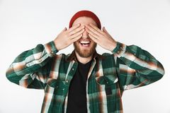 Portrait of smiling man wearing hat and plaid shirt covering his face with palms, while standing isolated over white background stock photos