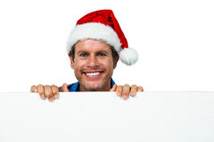 Portrait of smiling man wearing Santa hat. Against white background Stock Images