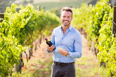 Portrait of smiling man with wine bottle using phone. At vineyard on sunny day Stock Images