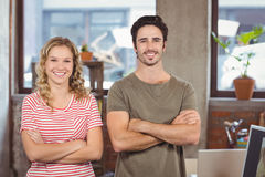 Portrait of smiling man and woman with arms crossed standing in office Stock Images