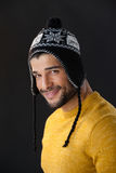 Portrait of smiling man in wooly hat. Against black background Royalty Free Stock Photo