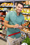 Portrait of smiling man writing on his notepad in aisle Stock Photography