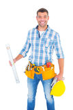 Portrait of smiling manual worker holding spirit level Royalty Free Stock Photos