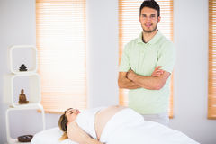 Portrait of smiling masseur standing behind his pregnant patient Stock Photo