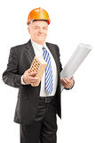 Portrait of a smiling mature architect holding a brick Stock Photography