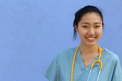 Portrait of smiling mature Asian doctor with stethoscope isolated over blue background with copy space Stock Photo