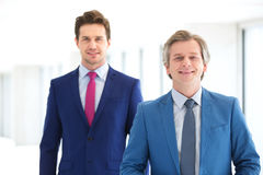 Portrait of smiling mature businessman and male colleague in office Royalty Free Stock Photo
