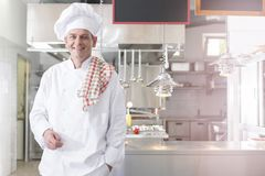 Portrait of smiling mature chef standing against kitchen in restaurant stock image