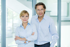 Portrait of smiling, mature, confident business partners in blue shirts looking at camera Stock Image