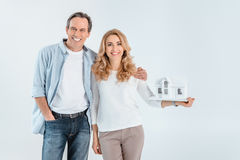 Portrait of smiling mature couple with house model stock image