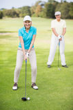 Portrait of smiling mature couple playing golf Stock Image