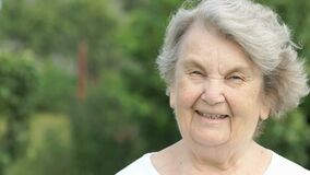 Portrait of smiling mature elderly woman outdoors stock video footage