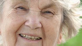 Portrait of smiling mature elderly woman. Close-up stock footage