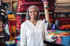Smiling mature woman standing by cloth in her fabric store Stock Photo